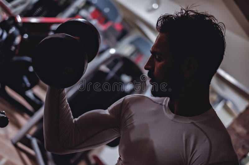 Homme faisant des boucles de biceps photos stock