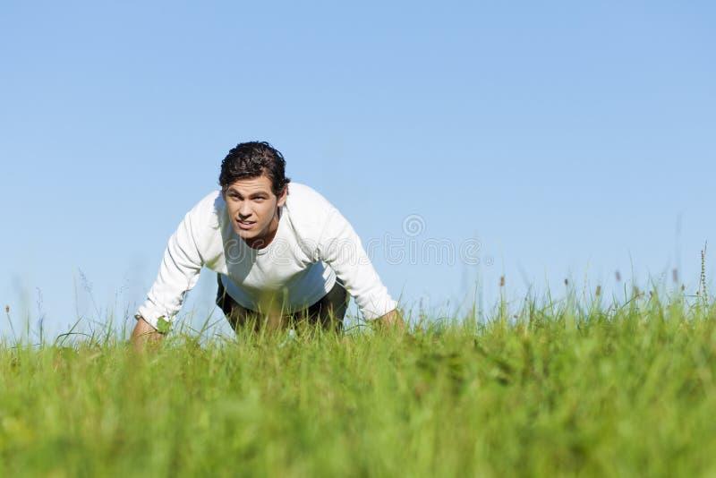 Homme faisant des pousées en herbe d'été photographie stock