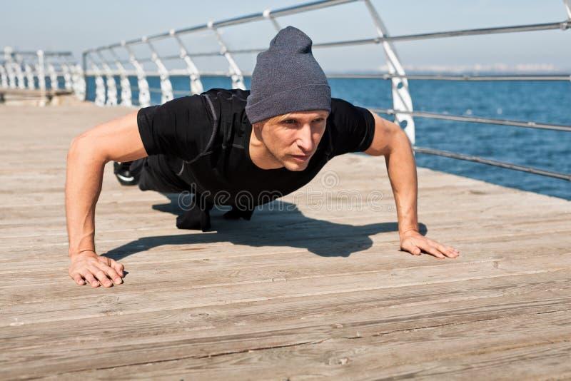 Homme faisant des pousées sur le bord de mer image libre de droits