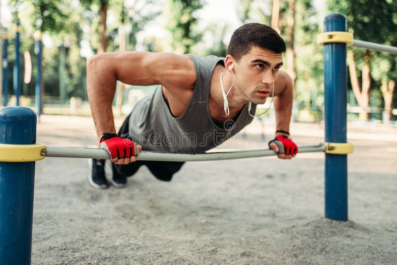 Homme faisant l'exercice de pompe utilisant la barre horizontale image libre de droits
