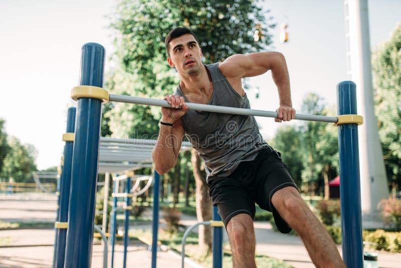Homme faisant l'exercice sur la barre horizontale extérieure photo stock