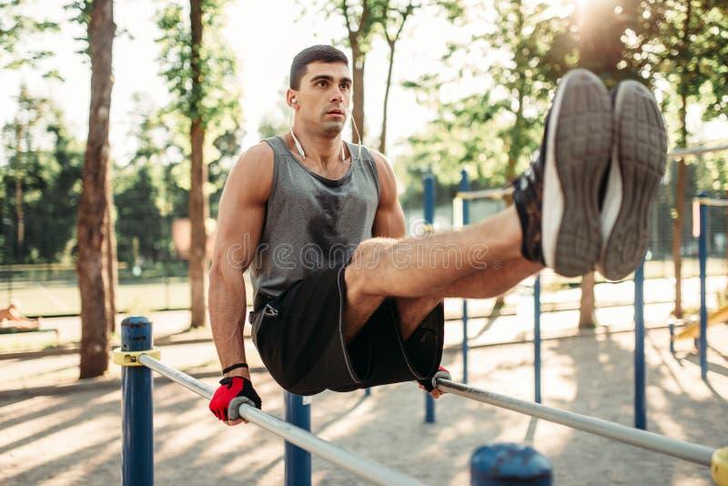 Homme faisant l'exercice sur la presse utilisant des barres parallèles photo stock