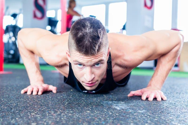 Homme faisant la pompe dans le gymnase de forme physique de sport photographie stock libre de droits