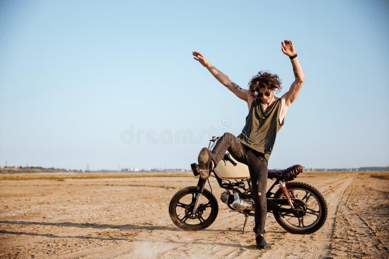 Homme faisant la poussière se tenant près de sa moto image libre de droits