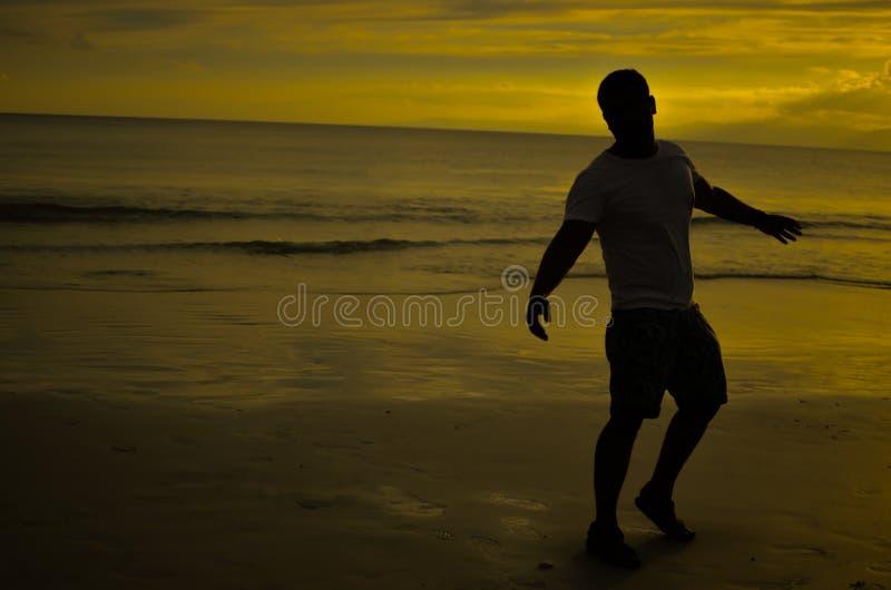 Homme faisant le geste ouvert de bras sous le coucher de soleil photo libre de droits
