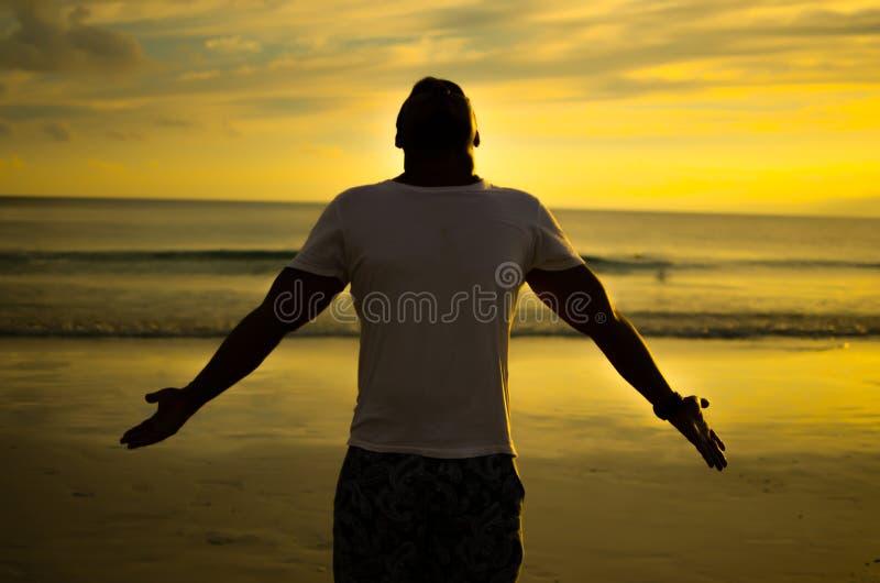 Homme faisant le geste ouvert de bras sous le coucher de soleil image stock