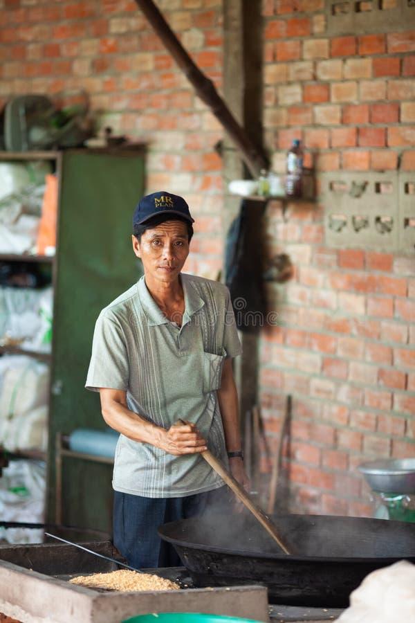 Homme faisant le maïs éclaté de riz au Vietnam images stock