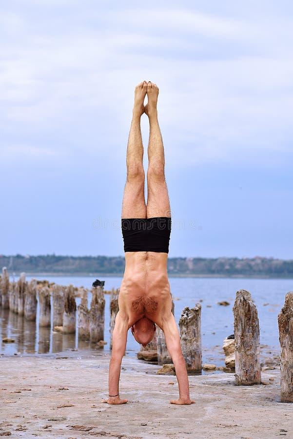Homme faisant le yoga se tenant sur des mains photographie stock