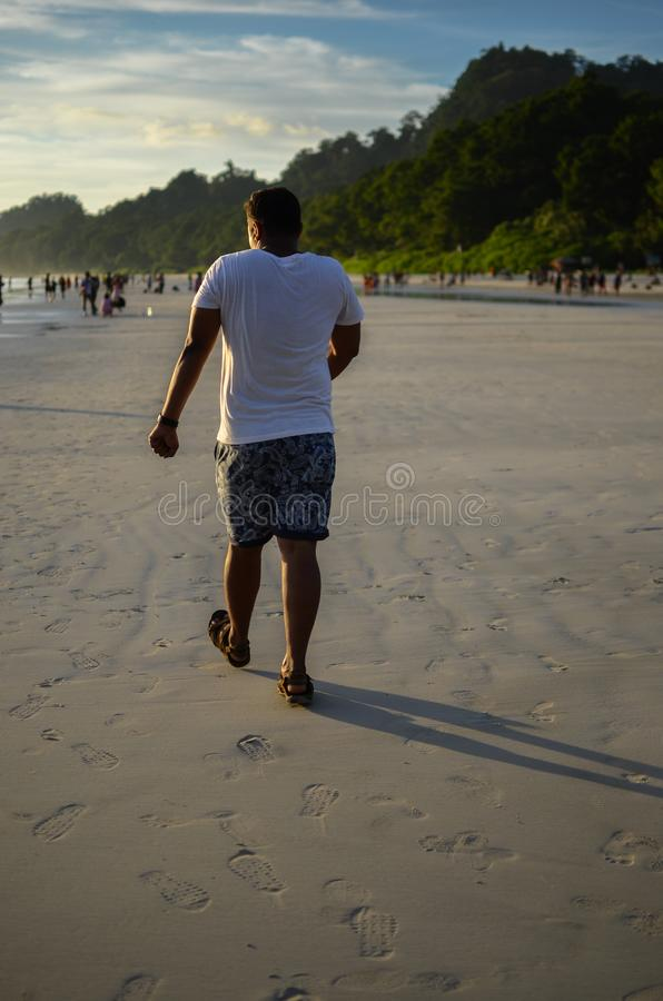 Homme faisant une promenade drôle sur une plage photo stock