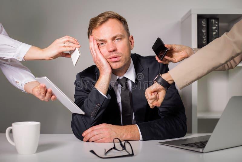 Homme fatigué étant surchargé au travail images stock