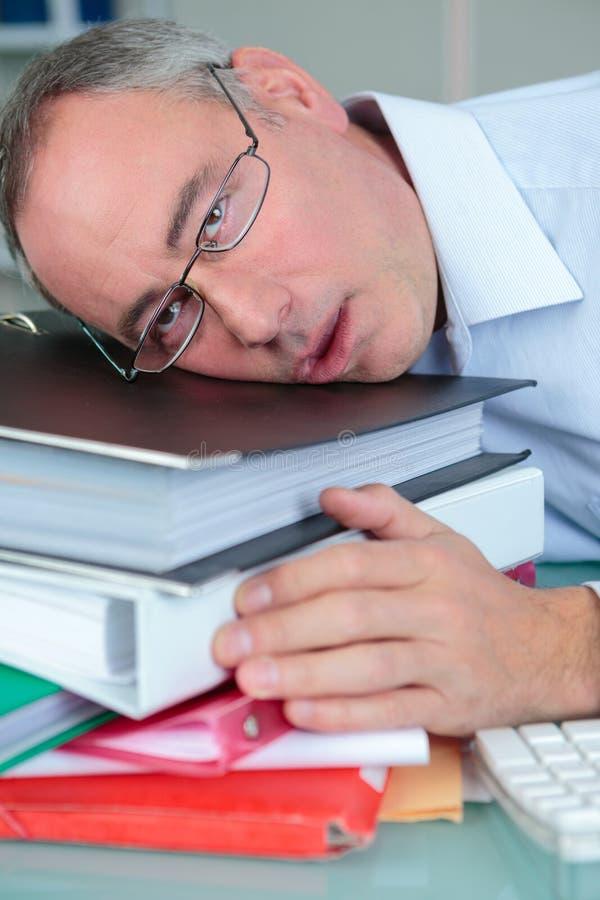 Homme fatigué avec des livres de pile images libres de droits
