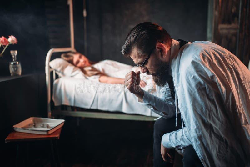 Homme fatigué contre la femme malade dans le lit d'hôpital image stock