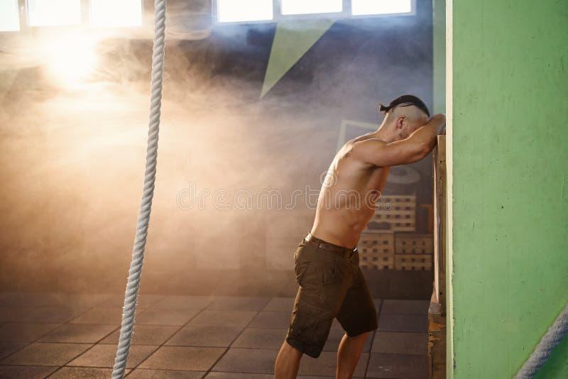 Homme fatigué de sport se reposant après exercice dur dans le gymnase photos libres de droits