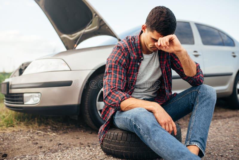 Homme fatigué s'asseyant sur le pneu, voiture cassée photos libres de droits