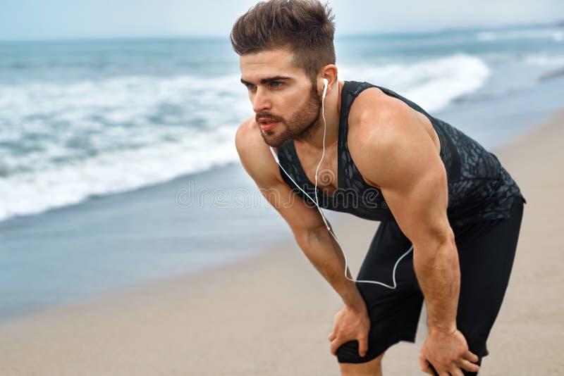 Homme fatigué se reposant après fonctionnement sur la plage Séance d'entraînement de sports extérieure images stock