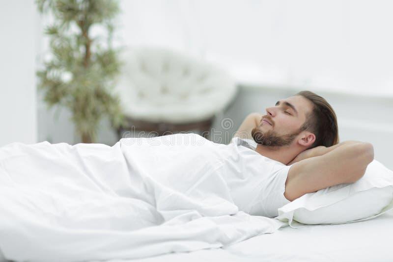 Homme fatigué se reposant sur un lit confortable image libre de droits