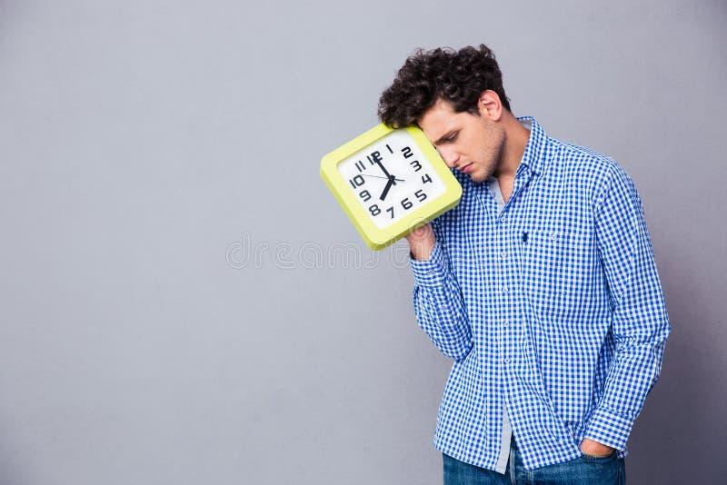 Homme fatigué tenant la grande horloge photos libres de droits