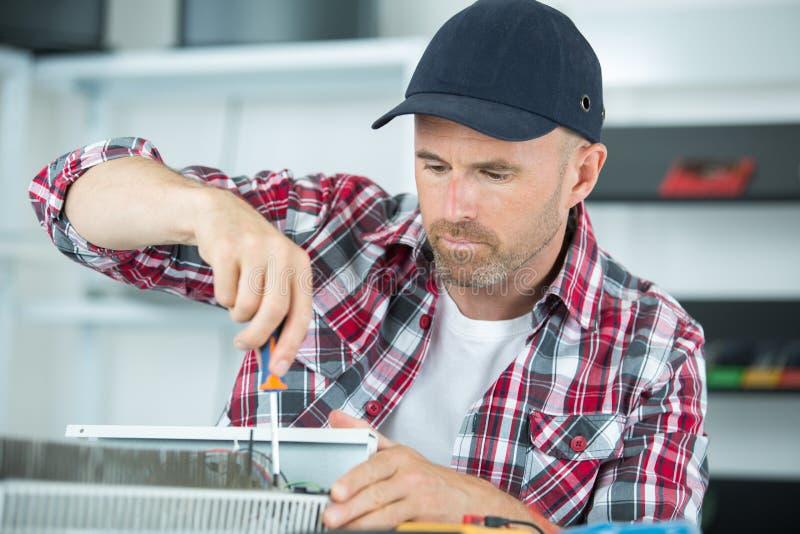 Homme fixant le vieil ordinateur de bureau utilisant le tournevis photos libres de droits