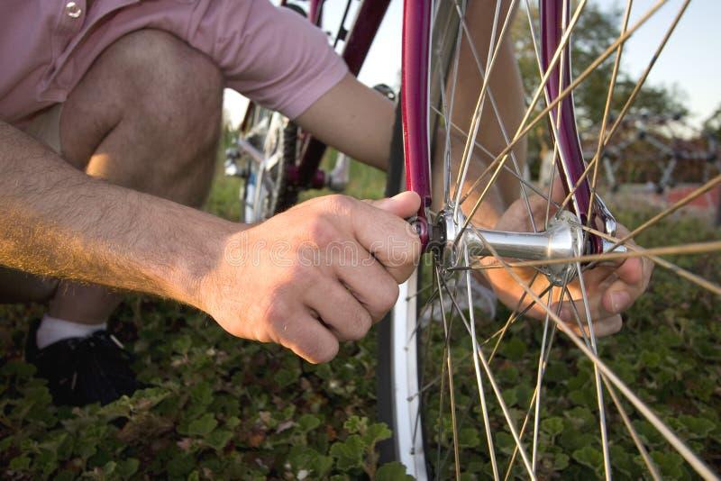 Homme fixant un vélo - horizontal photographie stock libre de droits