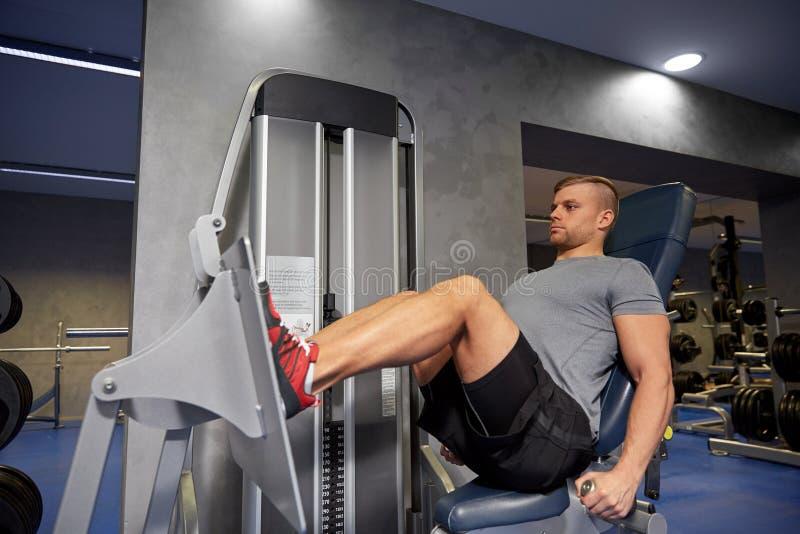 Homme fléchissant des muscles de jambe sur la machine de gymnase photographie stock libre de droits