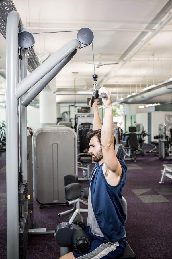 Homme focalisé à l'aide de la machine de poids pour des bras photo stock