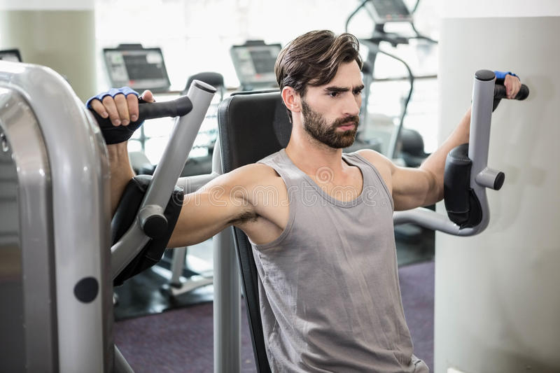 Homme focalisé à l'aide de la machine de poids pour des bras photo libre de droits