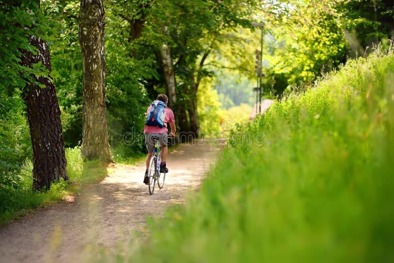 Homme folâtre faisant un cycle en parc ensoleillé dans le jour d'été chaud La Suisse, l'Europe photo stock
