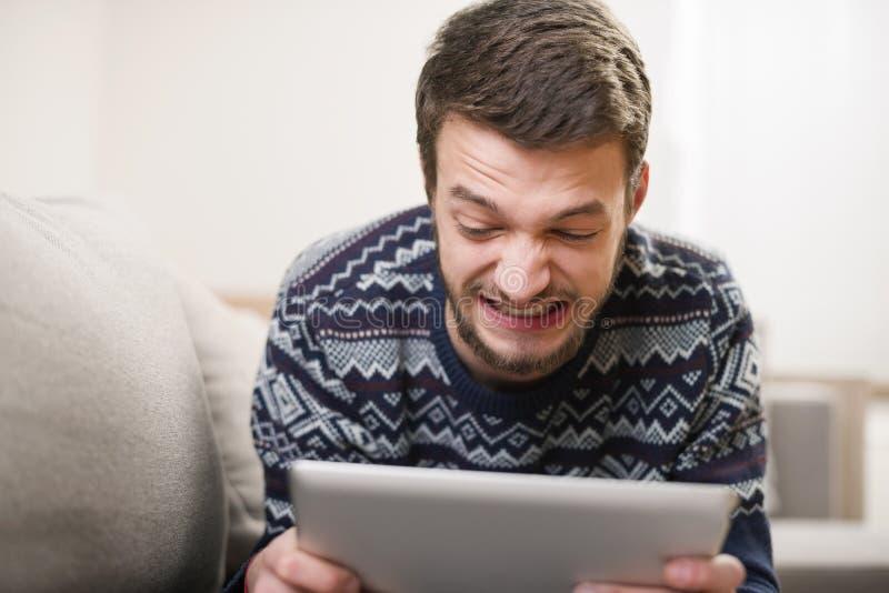Homme fol avec le comprimé numérique se trouvant sur le divan photo libre de droits