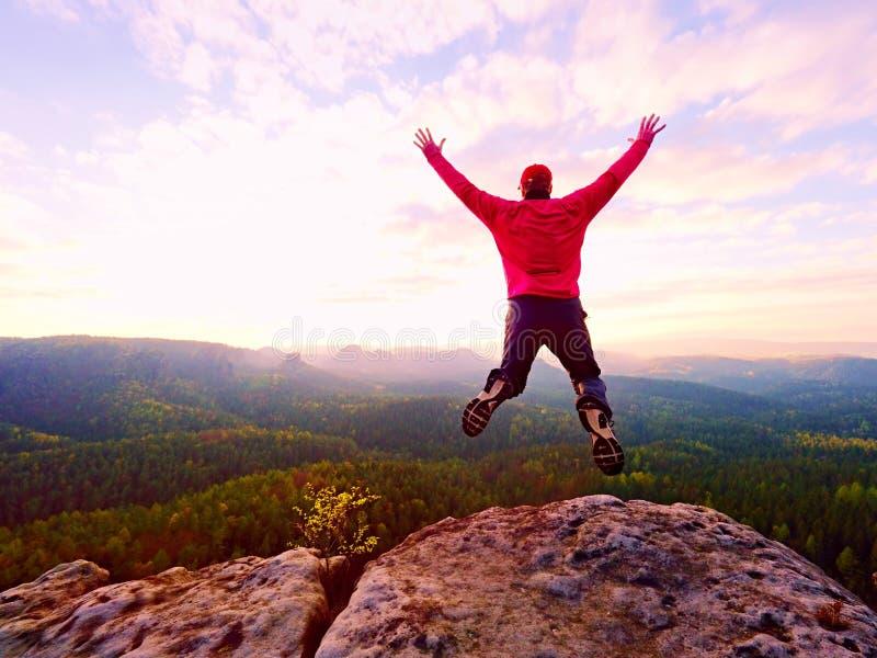 Homme fol Le randonneur saute sur la crête rocheuse Humeur merveilleuse en montagnes rocheuses, photo stock