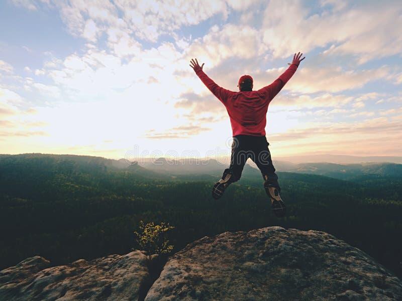 Homme fol Le randonneur saute sur la crête rocheuse Humeur merveilleuse en montagnes rocheuses, photographie stock