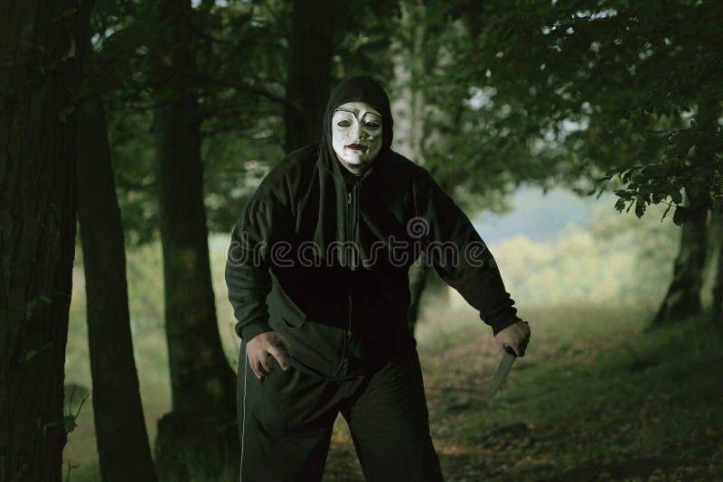 Homme fol masqué avec un couteau image stock