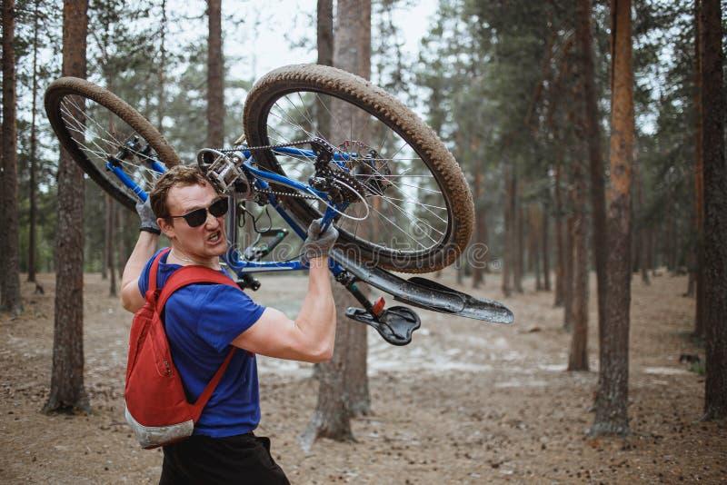 Homme fort bel regardant la caméra tout en marchant dans la forêt et tenant des frais généraux de vélo Concept d'?nergie photographie stock libre de droits