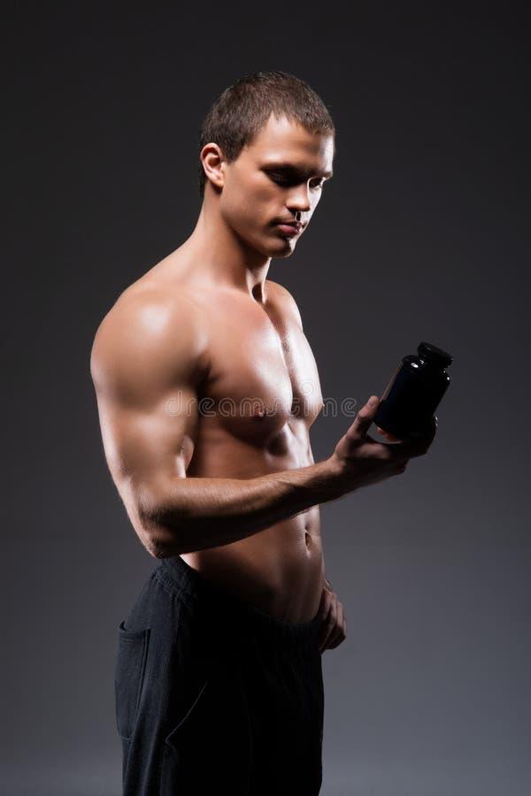 Homme fort, convenable et sportif de bodybuilder avec une bouteille de proteine photo libre de droits
