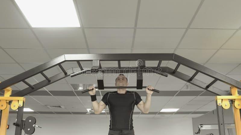 Homme fort d'athlète faisant des exercices sur la barre horizontale dans le gymnase photo libre de droits
