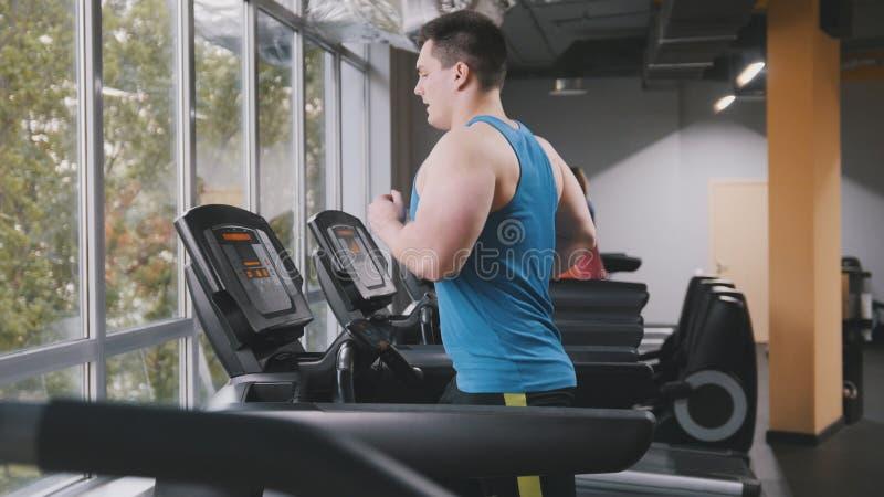 Homme fort dans le gymnase - bodybuilder courant sur la voie courante dans le gymnase images libres de droits