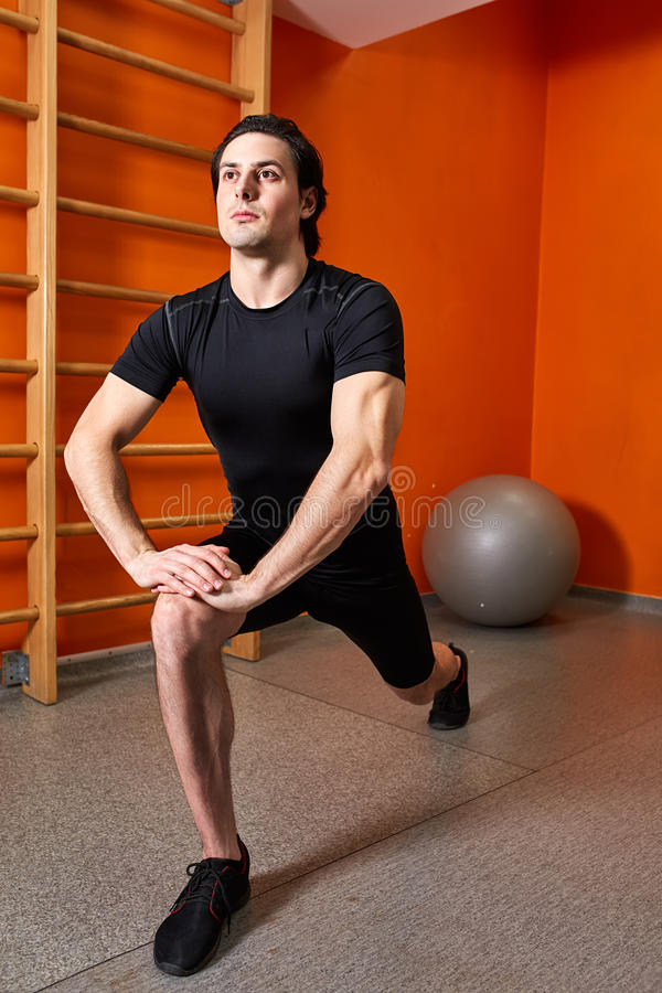Homme fort dans le sportwear noir étirant des jambes avant séance d'entraînement de gymnase contre le mur orange lumineux photo stock