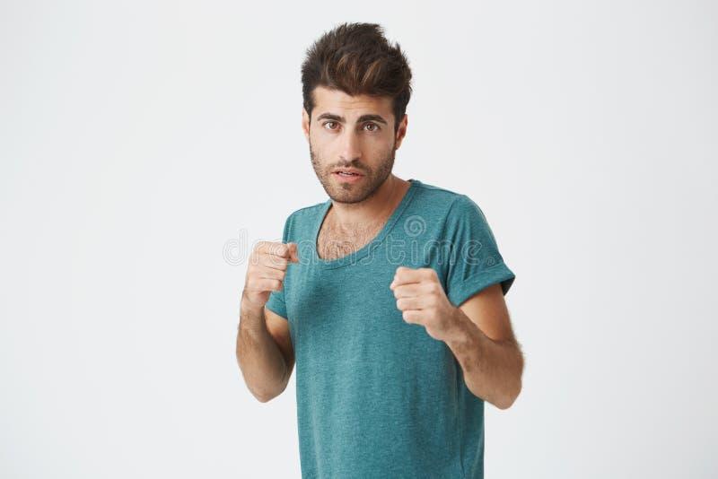 Homme fort et résolu dans le T-shirt bleu avec la barbe se tenant dans une position de combat sur un fond blanc Étudiant mâle photos stock