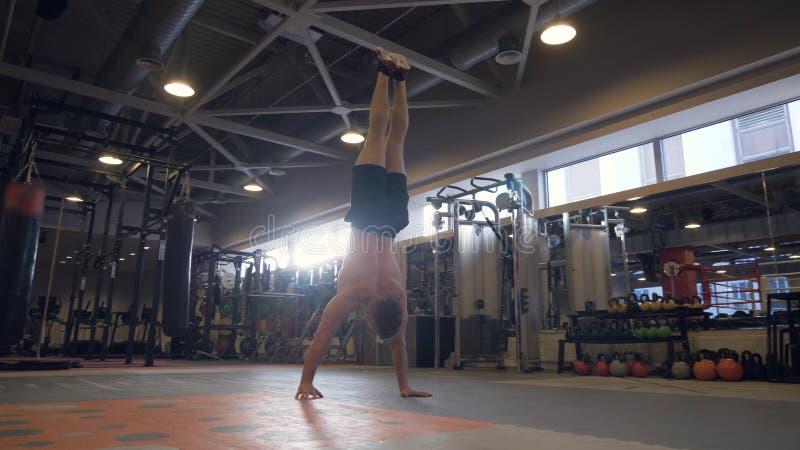 Homme fort marchant en main pendant la formation de crossfit dans le centre de fitness photos stock