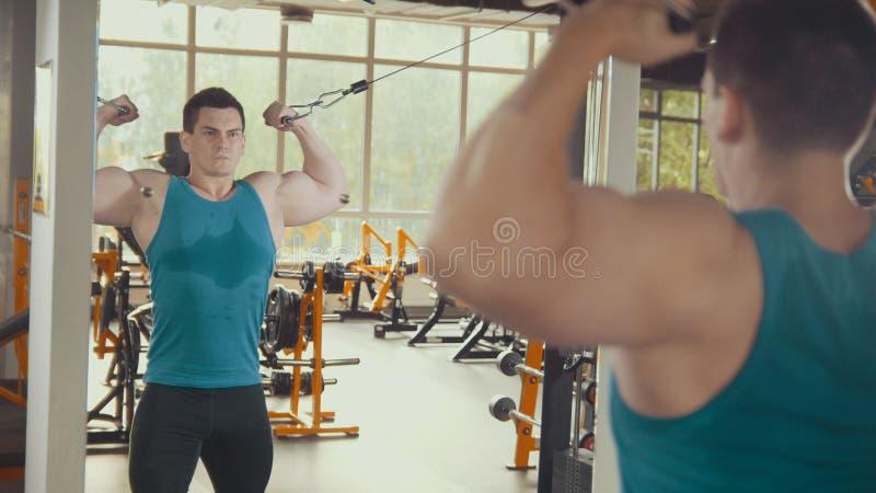 Homme fort s'exerçant devant le miroir dans le gymnase photo stock