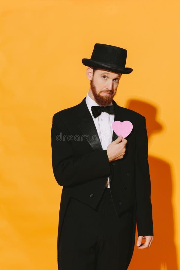Homme frais avec une barbe orange et un coeur rose recherchant l'amour image stock