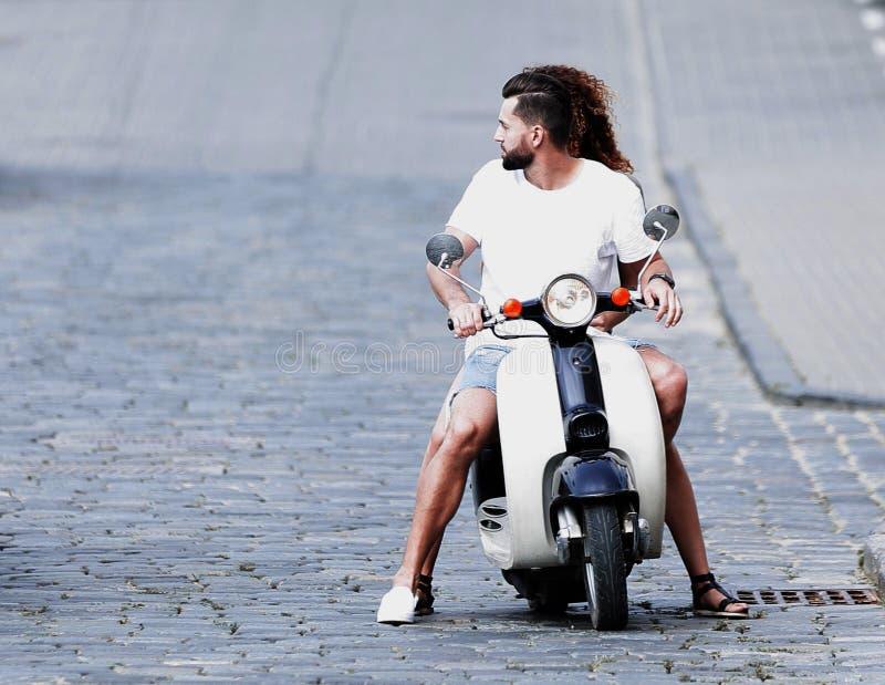 Homme frais et belle équitation de fille sur le scooter avec l'expression photographie stock libre de droits