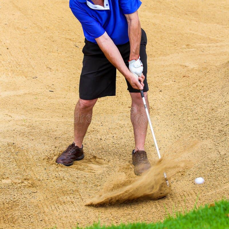 Homme frappant la boule de golf hors d'une soute images stock