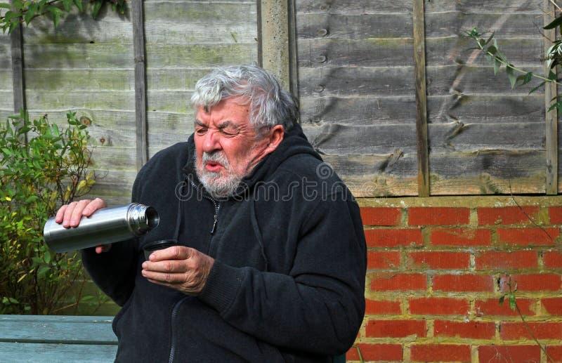 Homme froid tenant un flacon et un boire de vide image libre de droits