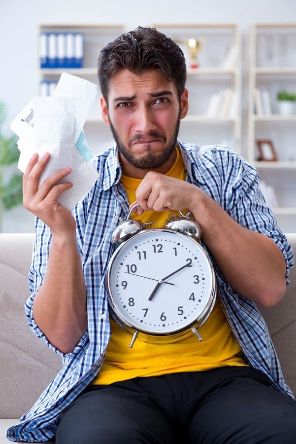 Homme frustré aux factures qu'il doit payer dans le conce de gestion du temps photographie stock libre de droits