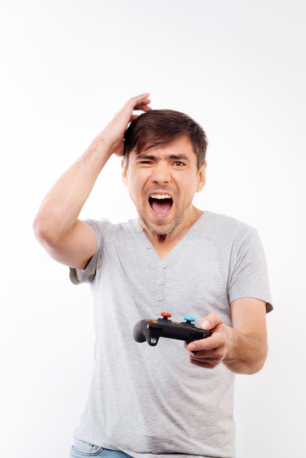 Homme frustrant étant dérangé au sujet du jeu vidéo perdant photo stock