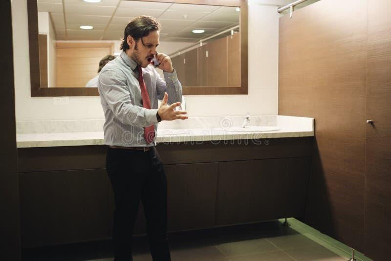 Homme furieux d'affaires criant au téléphone portable dans des toilettes de bureau images stock