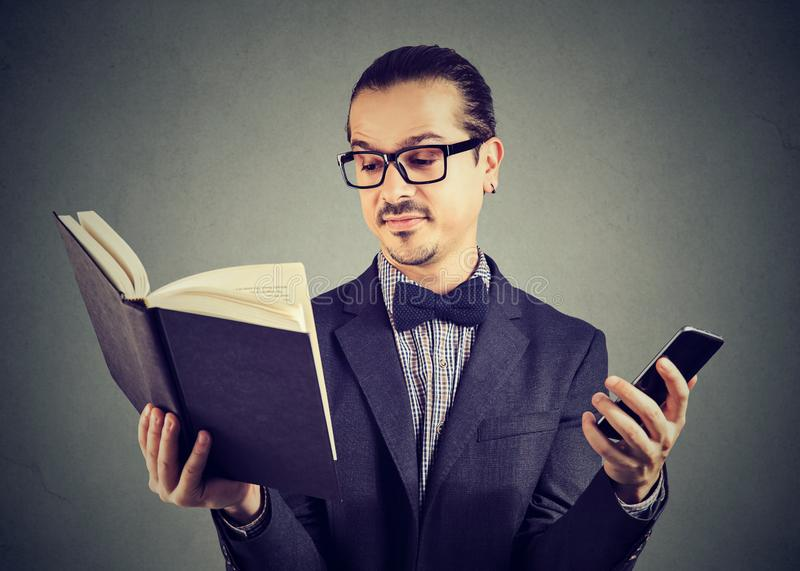 Homme futé avec le livre de lecture de téléphone image libre de droits