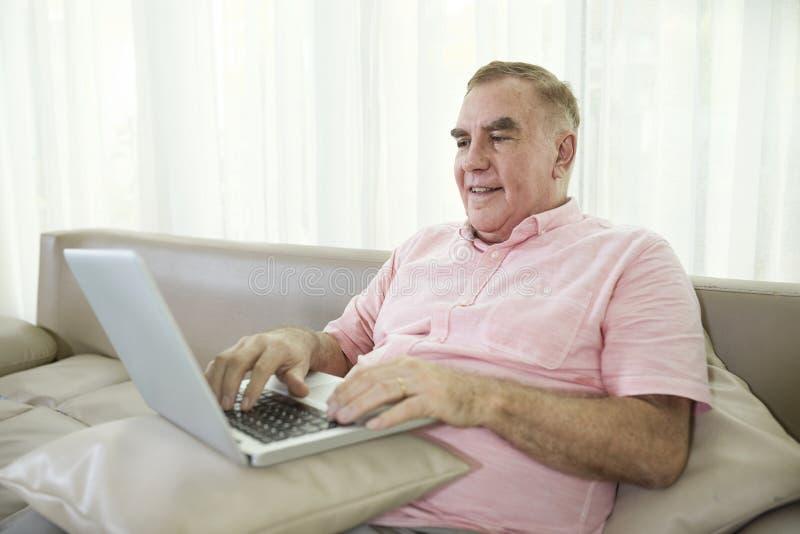 Homme ?g? travaillant sur l'ordinateur portable images stock