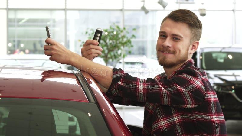 Homme gai à l'aide du téléphone intelligent montrant des clés de voiture à l'appareil-photo posant au concessionnaire photographie stock libre de droits