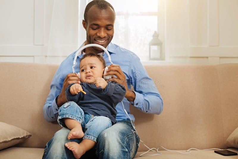 Homme gai écoutant la musique avec son bébé photographie stock